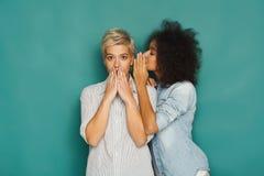 Junge Frau, die ihrem Freund einigen Geheimnissen sagt Lizenzfreie Stockbilder