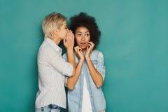 Junge Frau, die ihrem Freund einigen Geheimnissen sagt Stockfotos