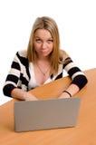 Junge Frau, die an ihrem Laptop arbeitet stockfoto