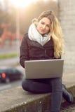 Junge Frau, die an ihrem Laptop arbeitet Stockbilder