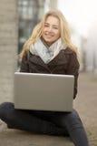 Junge Frau, die an ihrem Laptop arbeitet Stockfotografie