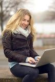 Junge Frau, die an ihrem Laptop arbeitet Lizenzfreie Stockfotografie