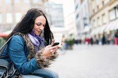 Junge Frau, die an ihrem Telefon simst Stockfotos