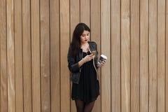 Junge Frau, die an ihrem Zelltelefon plaudert, bei der Stellung gegen hölzernen Wandhintergrund mit Kopienraumbereich, Lizenzfreies Stockfoto