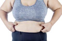 Junge Frau, die ihren Bauch auf Studio klemmt lizenzfreies stockfoto