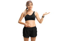 Junge Frau, die ihren Bauch fett berührt und mit der Hand gestikuliert stockfoto