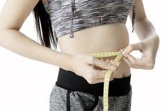 Junge Frau, die ihren dünnen Bauch misst Lizenzfreies Stockbild