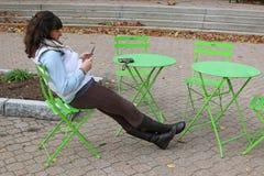 Junge Frau, die ihren Datenfernsprecher verwendet Lizenzfreie Stockfotografie