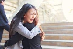Junge Frau, die ihren deprimierten Freund umarmend traurig und geschrieen worden sein würden Stockfoto
