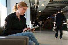 Junge Frau, die ihren digitalen Tabletten-PC an einem Flughafenaufenthaltsraum verwendet stockfotos