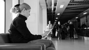 Junge Frau, die ihren digitalen Tabletten-PC an einem Flughafenaufenthaltsraum verwendet Stockbild