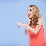 Junge Frau, die ihren Finger auf etwas zeigt Lizenzfreie Stockbilder