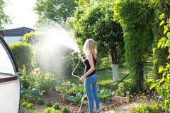 Junge Frau, die ihren Garten gießt Stockfoto