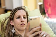 Junge Frau, die ihren Handy betrachtet lizenzfreie stockfotos