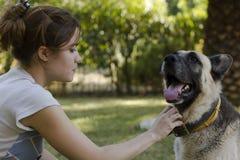 Junge Frau, die ihren Hund streichelt Lizenzfreie Stockbilder