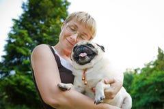Junge Frau, die ihren Hund umarmt Lizenzfreie Stockfotografie