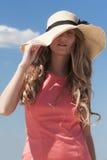 Junge Frau, die ihren Hut mit einer Hand hält Stockfoto