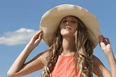 Junge Frau, die ihren Hut mit zwei Händen hält Lizenzfreies Stockbild