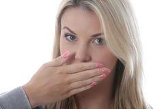 Junge Frau, die ihren Mund bedeckt Stockfotografie