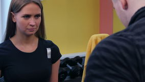Junge Frau, die ihren persönlichen Trainer aufpasst, Übung in der Turnhalle zu tun stock video footage