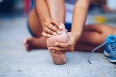 Junge Frau, die ihren schmerzlichen Fuß vom Trainieren massiert Stockfotos