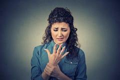 Junge Frau, die ihren schmerzlichen Handgelenkarm hält Stockfotos