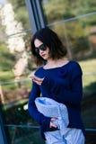 Junge Frau, die ihren Smartphone auf Terrasse verwendet stockfotografie