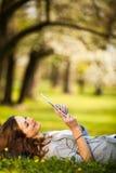 Junge Frau, die ihren Tablet-Computer bei draußen sich entspannen verwendet Stockbild