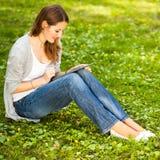 Junge Frau, die ihren Tablet-Computer bei draußen sich entspannen verwendet Stockfotos