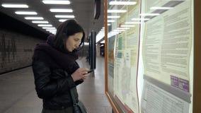 Junge Frau, die ihren Weg an der Bahnstation überprüft Junges Mädchen, das Karten-Platte und ihr Smartphone überprüft stock video footage