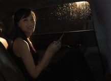 Junge Frau, die im Auto, an ihrem Telefon sitzt und die Kamera auf einer regnerischen Nacht in Peking betrachtet Stockfotografie