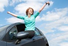 Junge Frau, die im Auto sitzt und einen Schlüssel gegen blaue SK hält Lizenzfreie Stockfotografie