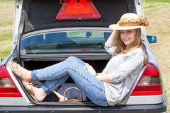 Junge Frau, die im Autokofferraum sitzt Stockbilder