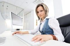 Junge Frau, die im Büro arbeitet Lizenzfreie Stockfotos