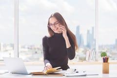 Junge Frau, die im Büro arbeitet Stockbilder