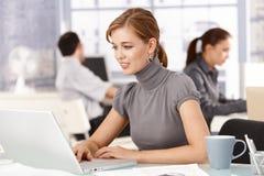Junge Frau, die im Büro unter Verwendung des Laptoplächelns arbeitet Lizenzfreies Stockbild