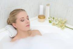 Junge Frau, die im Bad mit Schaum sich entspannt Stockbild