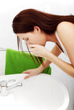Junge Frau, die im Badezimmer krank sich fühlt. Stockfoto