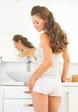 Junge Frau, die im Badezimmer steht Lizenzfreies Stockbild