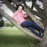 Junge Frau, die im Baum sitzt Stockfotos