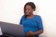 Junge Frau, die im Bett arbeitet auf Laptop sitzt lizenzfreie stockbilder