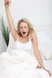 Junge Frau, die im Bett ausdehnt und gähnt Lizenzfreie Stockbilder