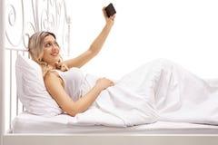 Junge Frau, die im Bett liegt und ein selfie nimmt Lizenzfreie Stockbilder