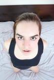 Junge Frau, die im Bett liegt und zu den Männern genital schaut stockbild