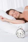 Junge Frau, die im Bett mit Alarmuhr schläft Lizenzfreies Stockfoto