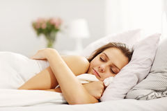 Junge Frau, die im Bett schläft lizenzfreie stockfotos
