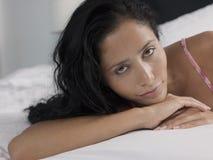 Junge Frau, die im Bett sich entspannt stockfotografie