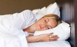 Junge Frau, die im Bett sich entspannt Lizenzfreie Stockbilder