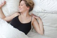 Junge Frau, die im Bett sich entspannt Stockbilder