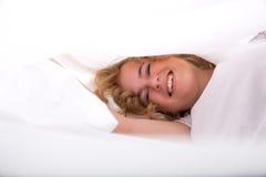 Junge Frau, die im Bett unter den Blättern sich versteckt Stockbilder